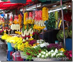 Strings of fresh flowers at a market stall.